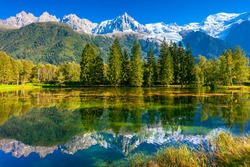 Early fall in Shamoni,  France. The snow-covered Alps and evergreen fir-trees are reflected in lake