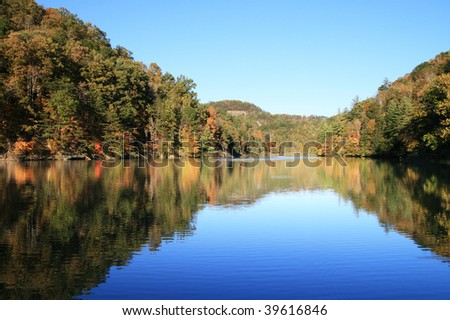 early fall reflection in Mill Creek Lake, Natural Bridge State Park, Kentucky with the leaves just starting to change color