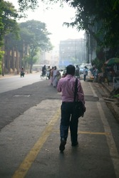 Early in the morning a man is seen walking, commuting to work at Churchgate, Mumbai, Maharashtra, India. Shot in October 2017
