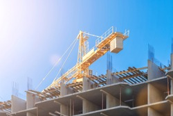 Early in the morning at sunrise, a yellow tower construction crane rises above an unfinished multi-story apartment building against a clear blue sky. The concept of modern monolithic construction.