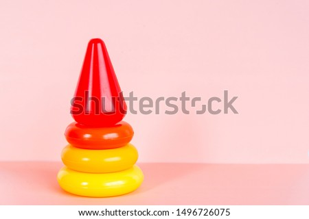 Early learning. Colorful geometric logic toy for geeks pyramid isolated on a pink background. Children's educational and educational games. Smart kids in kindergarten. Copy space