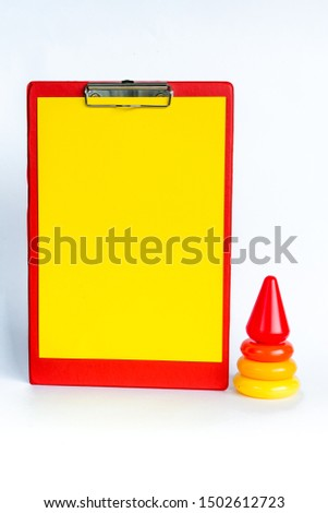 Early learning. Colorful geometric logic toy for geeks pyramid isolated on white background. Children's educational and educational games. Red tablet with yellow paper for teacher records. Copy space