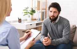 Early middle age crisis. Stressed young man talking to psychologist during individual therapy, free space