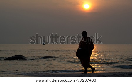 Early morning activity of monk on the beach at Huahin Thailand. - stock photo