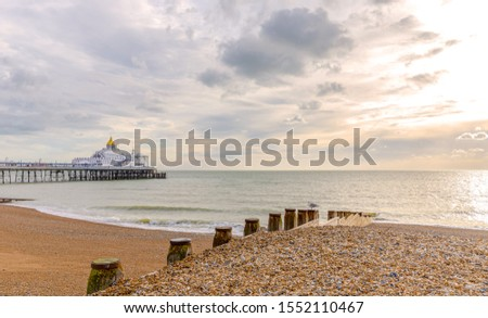 Early morning at a shingle beach in Eastbourne.  A wooden breakwater is in the foreground and a pier beyond. A dawn sky is above. #1552110467