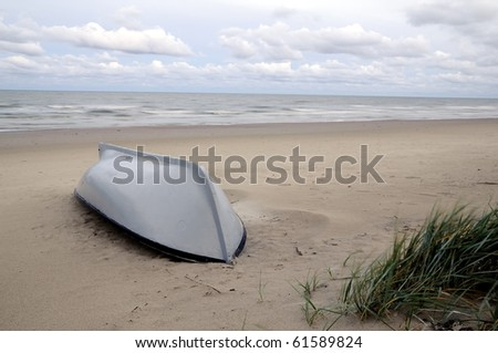 Early morning at Baltic sea after a night rain. Boat on a beach sand