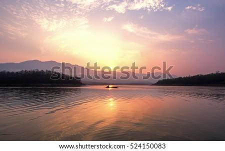 Shutterstock Early morning fishing boat navigation lamps. Fishermen fishing in the early morning golden light. Fisherman boat. Fisherman silhouette. Fisherman net.Srinakarin dam ,Thailand