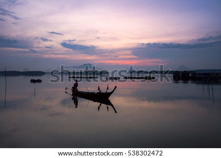 Shutterstock Early morning fishing boat navigation lamps,Fishermen fishing in the early morning golden light,,Photo Fisherman Silhouette, Ban Sam Chong Tai Village,Southern of Thailand