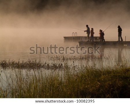 Early morning fishing in autumn on a lake as the mist rises from the water.
