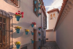 Early morning golden light over the quiet and quaint narrow cobblestone streets in old town (Albaicin or Arab Quarter) Granada, Spain, Andalusia.