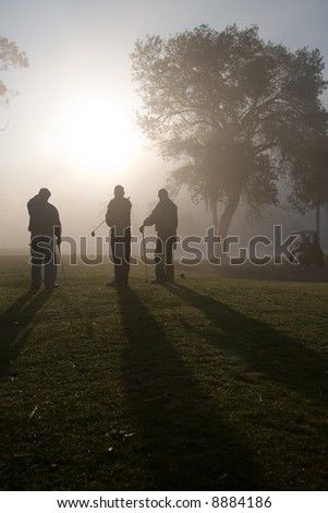 Early morning golfers silhouetted in a dense fog with a rising sun