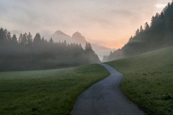 Early morning haze in the Alps. There is a narrow road leading to high mountains through a meadow. The high Alpine peaks are shrouded with light fog. The sky is turning pink. Daybreak. Calmness