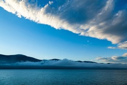 Early morning in the sea bay against the background of mountains, blue sky and fog in the distance rising above the water.