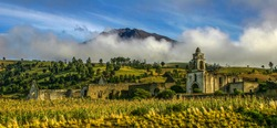 Early morning landscape shot of Hacienda Vista Hermosa in Puebla, Mexico as low clouds cover the background mountains.