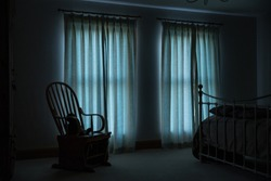 Early morning light enters through net curtains into a bedroom onto a whicker chair.