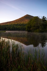Early morning light hitting the eastern side of Sharp Top Mountain as mist rises off of the reflection in Abbott Lake at Peaks of Otter.