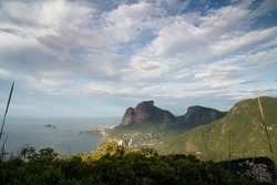 Early morning light over Pedra da Gavea and Sao Conrado Beach from Morro Dois Irmaos - Two Brothers Hill in Rio de Janeiro. There are clouds and blue sky with light on the tall rock mountain face.