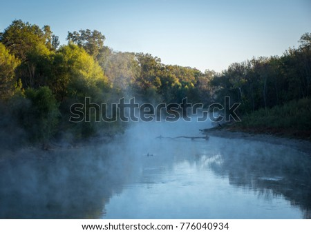 Early morning mist rises from water with reflection of surrounding trees in the Great Trinity Forest, Dallas, Texas
