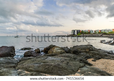 Early morning on the rocky foreshore at tropical Cannonvale Beach, Pioneer  Bay, Airlie Beach, the Whitsundays, Great Barrier Reef, Australia. High tide, cloudy sky. Holiday destination. Golden hour. #741536656