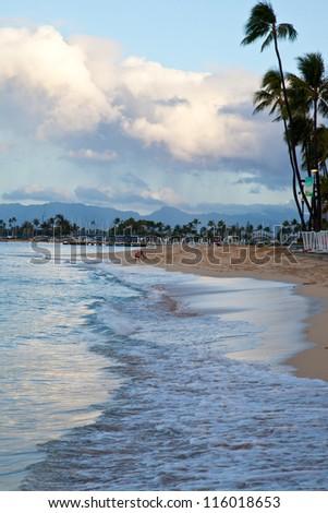 Early morning on Waikiki Beach. Palm trees and surf devoid of tourists. Oahu, Hawaii
