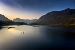 Early morning paddle boarders sail across Crummock Water a lake in the Lake District part of the UNESCO World Heritgae Centre in Cumbria.