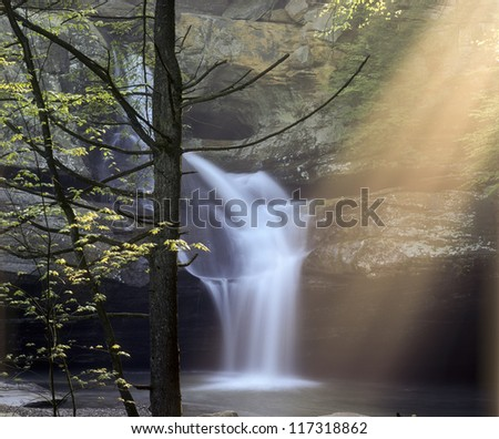 Early morning sun rays in mist at Cedar Falls  Hocking Hills State Park  Ohio