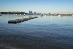 Early morning sunrise at Matilda Bay Reserve, Perth. The Perth city skyline can be seen in the distance with boats occupying the water in-front.