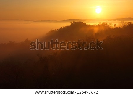 Early morning sunrise landscape with the sun beams playing over the slopes of the mountain.