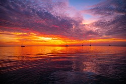 Early morning, sunrise over sea. Ocean sunset on sea water with a colorful vivid sunset sky and silhouettes of sailboat in the background
