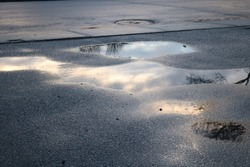 Early morning sunrise sky reflected in a puddle of water on pavement