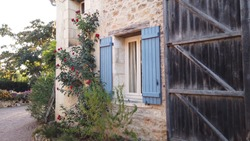 Early morning view of classic and typical French country house first showing sunshine moving left to wall with red roses and blue window shutters beautiful and romantic real estate sight