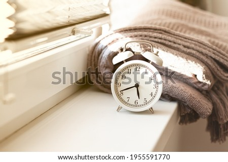 Early morning wake up concept. Retro alarm clock showing five forty five. Bed cover, window, sun light. Good start for efficient and sucessful day. Close up, white background. Copy space for text Stock photo ©