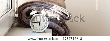 Early morning wake up concept. Retro alarm clock showing five forty five. Bed cover, window, sun light. Good start for efficient and sucessful day. Closeup white background. Copy space for text banner Stock photo ©