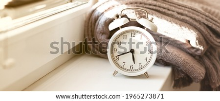 Early morning wake up concept. Retro alarm clock showing five forty five. Bed cover, window, sun light. Good start for efficient and sucessful day. Close up, white background. Copy space banner Stock photo ©