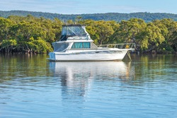 Early morning waterscape with a boat at Woy Woy, NSW, Australia.