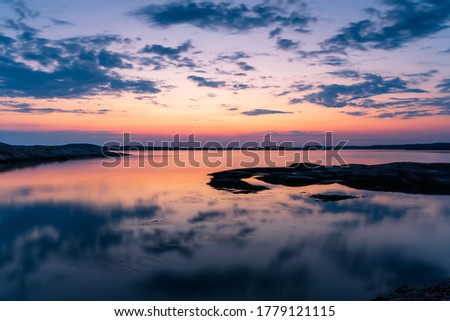 Early morning with a colorful sky and reflections in the ocean at the Swedish archipelago on the west coast, Bohuslän Foto stock ©