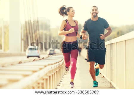 Early morning workout. Happy couple running across the bridge. Living healthy lifestyle.