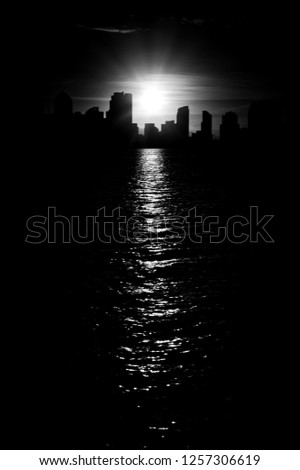 Early San Diego skyline in monochrome black and white with beautiful contours of down town cityscape with burning sun reflecting in sea water. More similar content is found in my portfolio.  #1257306619