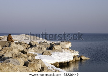 Early spring fishing from the still snow covered rocks at Ottawa beach on Lake Michigan