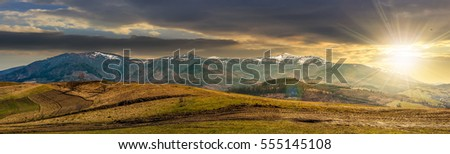 Early spring highland landscape. Panorama of rural fields on hill side in mountains with snowy peaks in evening light #555145108