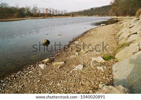 Early spring nature image on a sunny day of blue lake, strip of stony lakeside with sand, small and big stones and calm blue water, trees and blue sky with clouds #1040020891