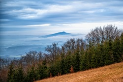 Early winter landscape with mountain meadow, forest and nice blue sky with silhouette of Jested hill in fog and clouds. Czech Paradise, Czech republic. Photo was taken at hill Kozakov.