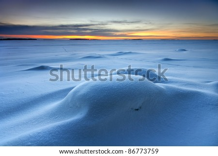 Early winter morning before sunrise in the snowy beach
