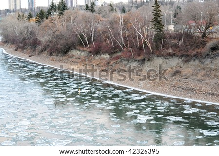 Early winter view of the north saskatchewan river with floating ice in city edmonton, alberta, canada
