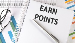 EARN POINTS text , pen and glasses on the chart,business concept