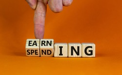 Earning or spending symbol. Businessman hand turns cubes and changes the word 'spending' to 'earning'. Beautiful orange background, copy space. Business and earning or spending concept.
