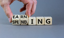 Earning or spending symbol. Businessman hand turns cubes and changes the word 'spending' to 'earning'. Beautiful grey background, copy space. Business and earning or spending concept.