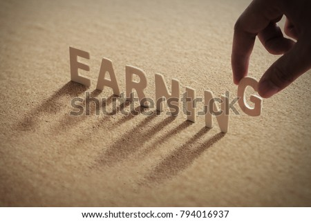 EARNING wood word on compressed or corkboard with human's finger at G letter.
