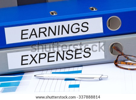 Earnings and Expenses - two binders with text on desk in the office #337888814