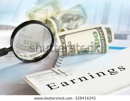 Earnings concept. Image of selective focus shot of magnifying glass, hundred dollar bills and
